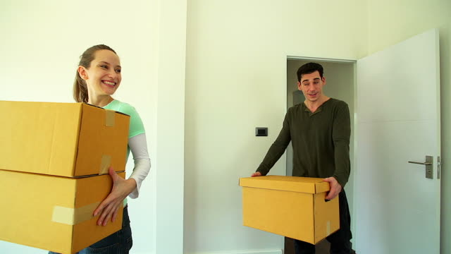 HD: Happy couple moving to new house with cardboard boxes