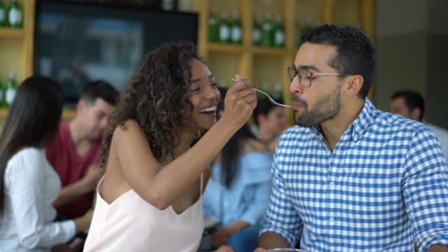 stockvideo's en b-roll-footage met gelukkige paar op een datum en partner voeden haar vriendje glimlachen - latijns amerikaanse en hispanic etniciteiten