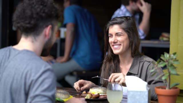 happy couple on a date at a restaurant eating lunch talking and smiling - south america stock videos & royalty-free footage