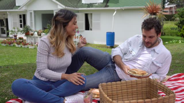 vidéos et rushes de couples heureux sur une date de pique-nique à leur arrière-cour appréciant un sandwich et des croustilles - panier pique nique