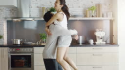Happy Couple on the Kitchen. Girl Jumps into Guy's Arms.