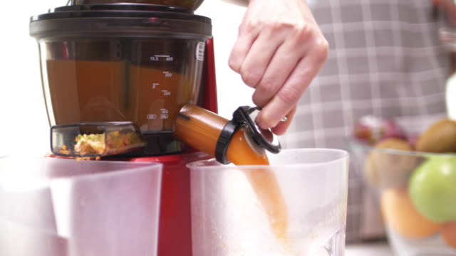 happy couple open juice from electric juicer in kitchen - electric juicer stock videos & royalty-free footage
