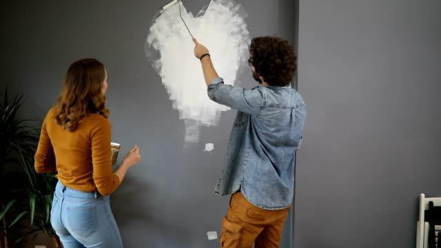 vídeos de stock e filmes b-roll de happy couple painting wall in a shape of heart - pano de protecção