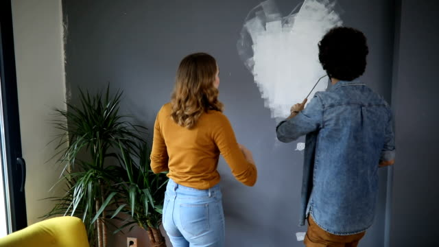 happy couple painting wall in a shape of heart - veduta di interni video stock e b–roll