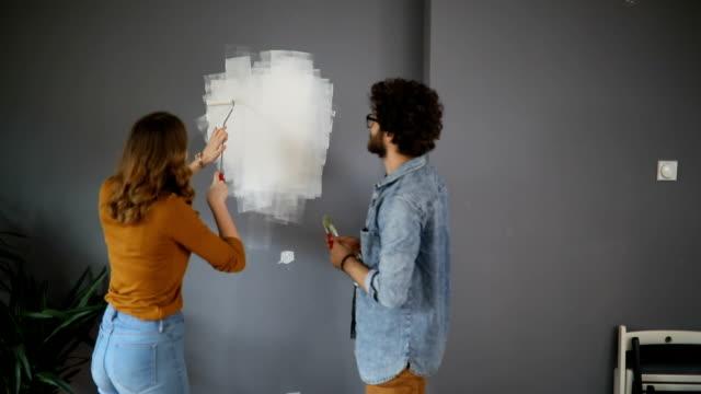 vídeos de stock e filmes b-roll de happy couple painting wall in their new home - pano de protecção