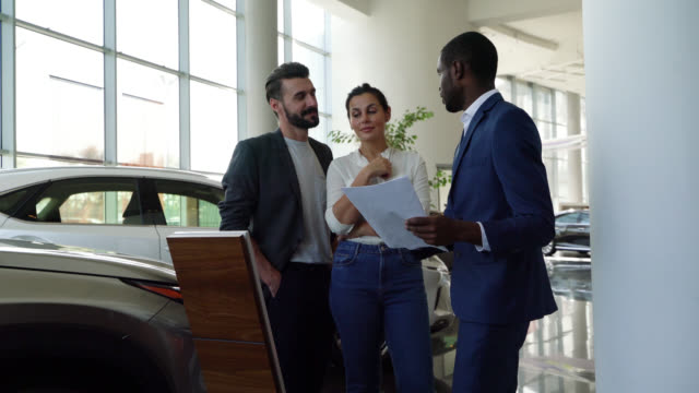 happy couple paying attention to black salesman talking about the properties of a car at a dealership - car showroom stock videos & royalty-free footage