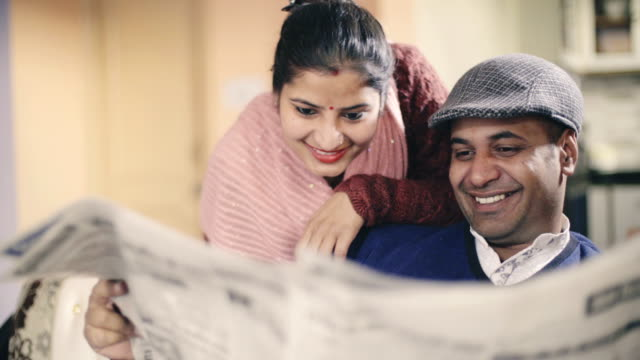 Happy couple reading newspaper together.