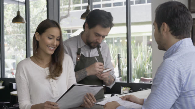 happy couple ready to make their order to the waiter - menu stock videos & royalty-free footage