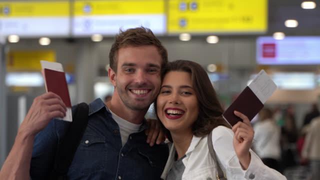 vídeos de stock, filmes e b-roll de pares felizes prontos para viajar no aeroporto que enfrenta a câmera que sorri mostrando seu passaporte e passagem de embarque - ticket