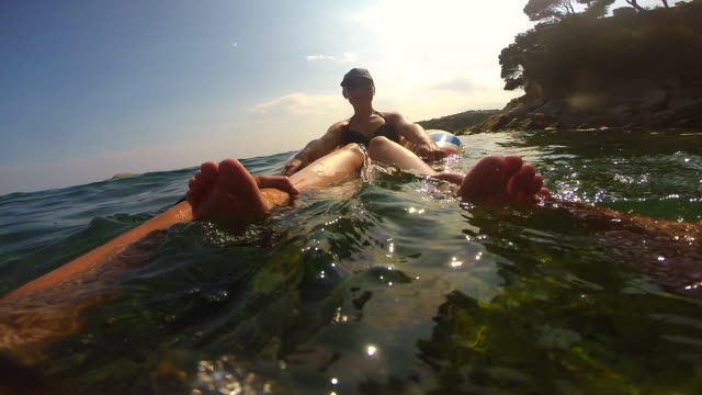 Happy couple recording footage from boyfriend personal perspective while swimming in the beautiful Costa Brava during summer vacations.