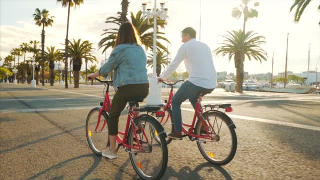 stockvideo's en b-roll-footage met gelukkig paar rijden fietsen rond de stad. - sunny