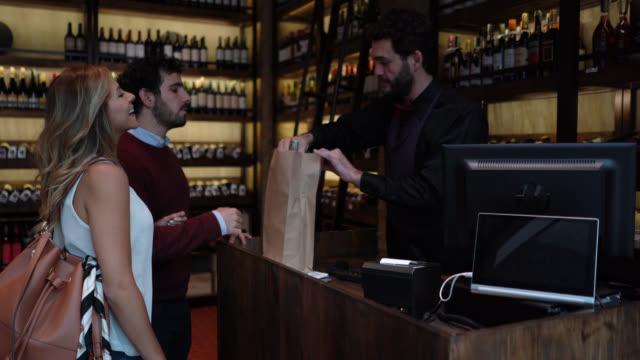 ワインセラーで紙袋にワインボトルを詰めるフレンドリーなソムリエに別れを告げる幸せなカップル - ワインバー点の映像素材/bロール