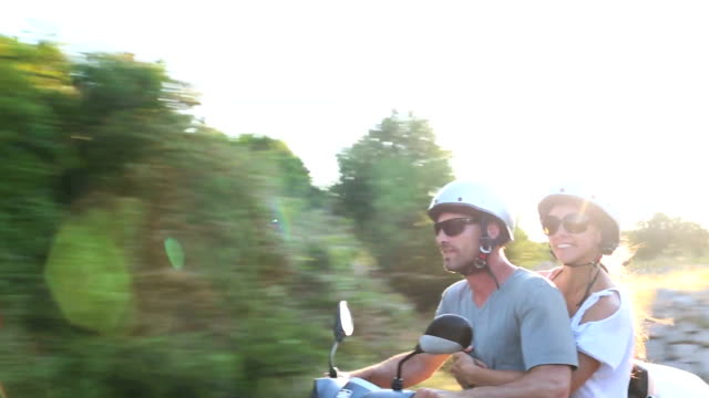 happy couple scooter adventure in golden evening sunlight - motor scooter stock videos & royalty-free footage