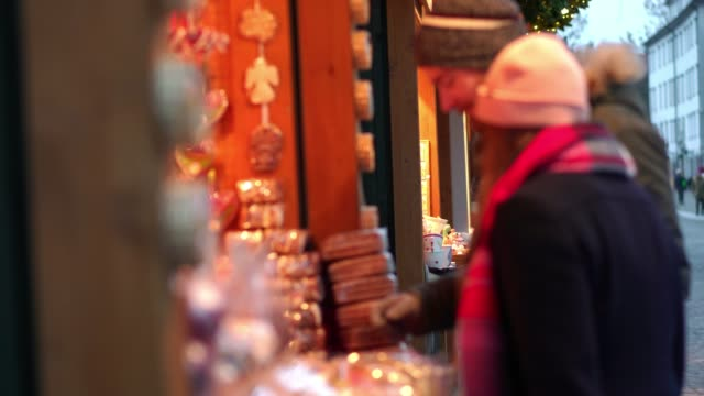 happy couple shopping for home meade gifts at christmas market - christmas market stock videos & royalty-free footage