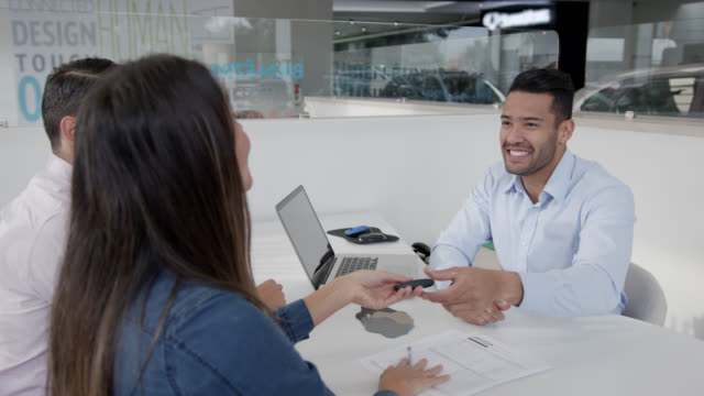 happy couple signing a form with friendly salesman at a car dealership while he hands them the key - car showroom stock videos & royalty-free footage