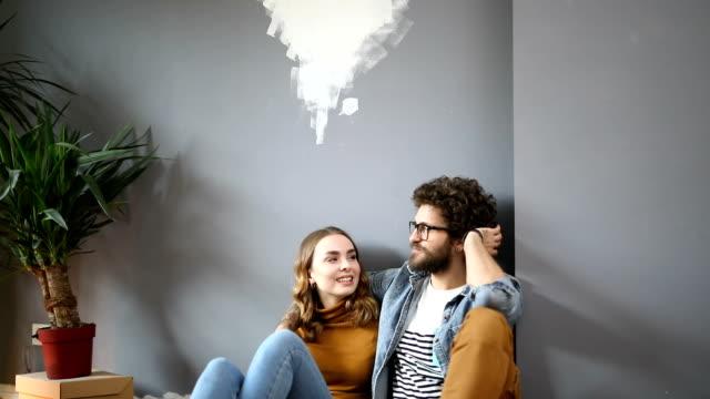 vídeos de stock e filmes b-roll de happy couple sitting on the floor and relaxing in their new home - pano de protecção