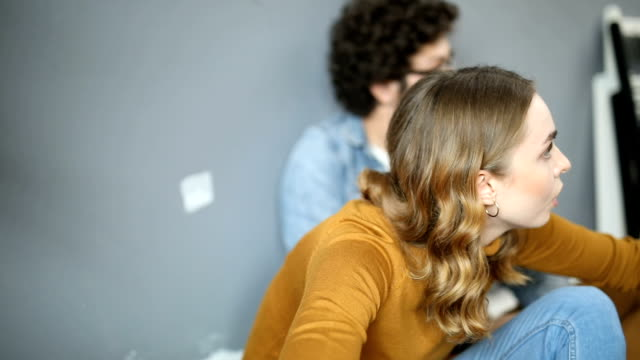 vídeos de stock e filmes b-roll de happy couple sitting on the floor and talking in their new home - pano de protecção