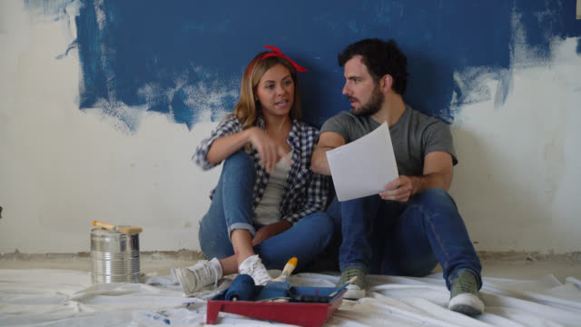 happy couple sitting on the floor looking at a design on paper during a home renovation - renovation stock videos & royalty-free footage