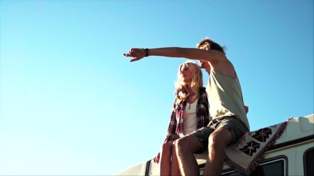 stockvideo's en b-roll-footage met gelukkig paar zittend op van dak tijdens zonnige dag - low angle view