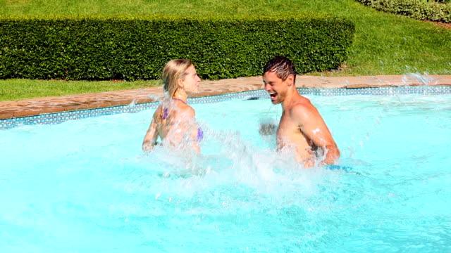 vidéos et rushes de heureux couple éclaboussures mutuellement dans la piscine - autre thème