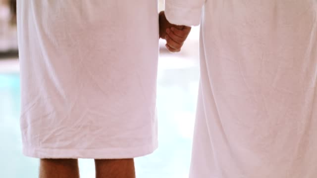 happy couple standing on poolside - bathrobe stock videos & royalty-free footage