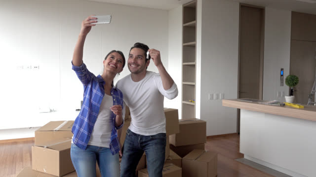 Happy couple taking a selfie at their new place