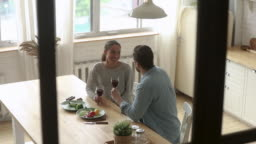 Happy couple talking clinking glasses sit at table at home