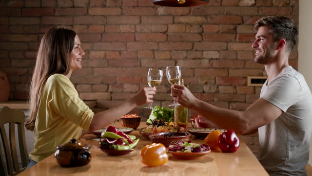 stockvideo's en b-roll-footage met gelukkig paar dat met wijn roostert tijdens lunch in eetkamer. - heteroseksueel koppel