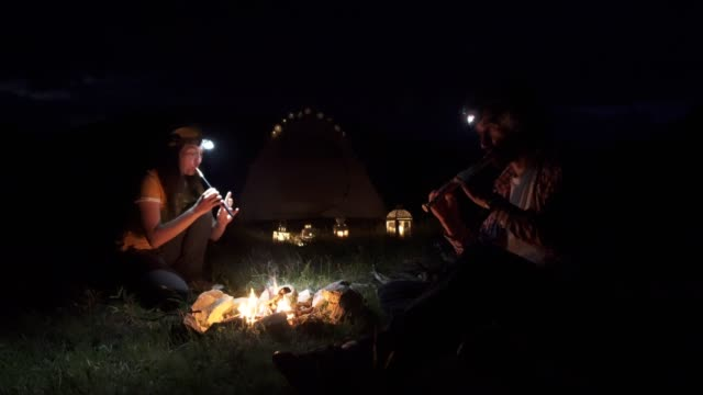Happy Couple Tourists Camping and Making a Campfire in the Nature. Adventure Surviving Outdoors in the Wilderness Area.