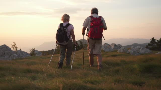 stockvideo's en b-roll-footage met gelukkige paar trekking op een berg - following moving activity