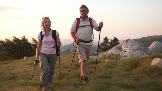 happy couple trekking on a mountain - active seniors stock videos & royalty-free footage