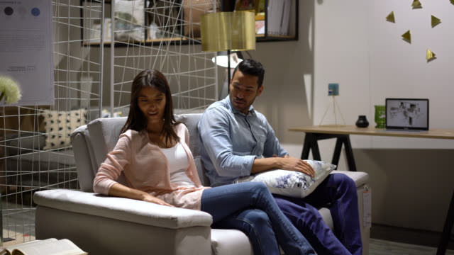 happy couple trying out a couch at a furniture store while talking - furniture stock videos & royalty-free footage