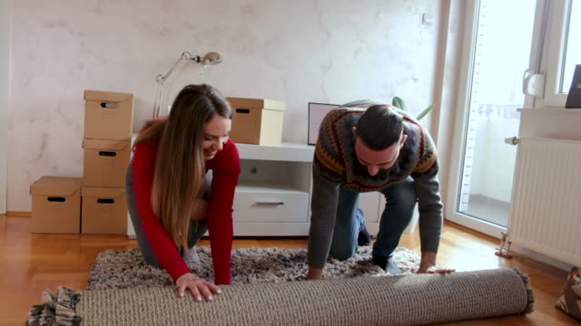happy couple unrolling carpet on floor at new home - rug stock videos & royalty-free footage