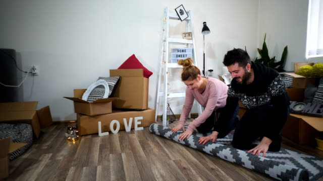 Happy couple unrolling carpet or rug on floor at home