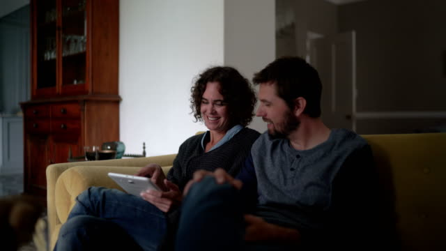 happy couple using digital tablet on sofa at home - mid adult couple stock videos & royalty-free footage
