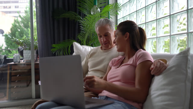 happy couple using laptop and checking correspondence while sitting on couch - examining stock videos & royalty-free footage