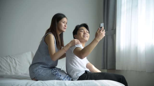 自分撮りやビデオ通話に携帯電話を使用して幸せなカップル - デート点の映像素材/bロール