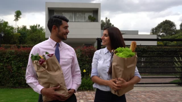 happy couple walking home carrying groceries while talking - paper bag stock videos & royalty-free footage