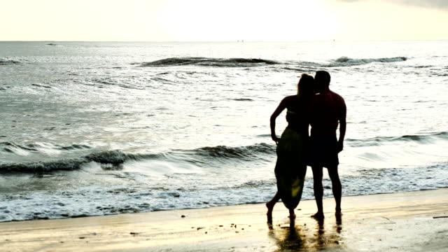 Happy couple walking on the beach. Romantic scenery. Sunset