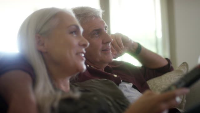 happy couple watching tv at home - 50 59 years stock videos & royalty-free footage