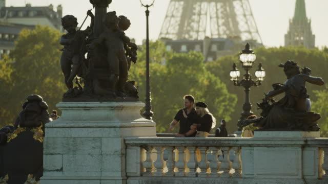 happy couple waving near statues on pont alexandre / paris, ile de france, france - brücke pont alexandre iii stock-videos und b-roll-filmmaterial