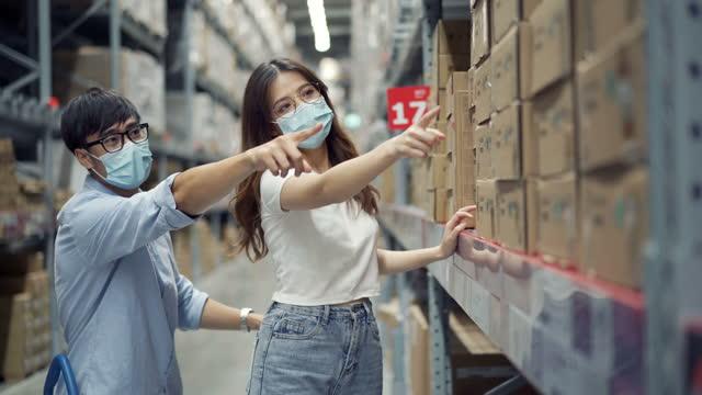 glückliches paar trägt schutzmaske beim einkaufen im lager - casual clothing stock-videos und b-roll-filmmaterial