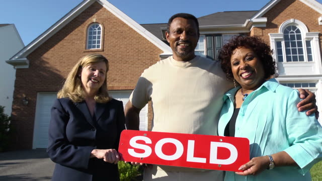 happy couple with agent holding sold sign - selling stock videos and b-roll footage