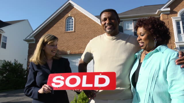 happy couple with agent holding sold sign - selling stock videos & royalty-free footage