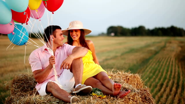 Coppia felice con palloncini nascondendo qualcosa.