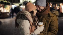 happy couple with coffee at christmas market