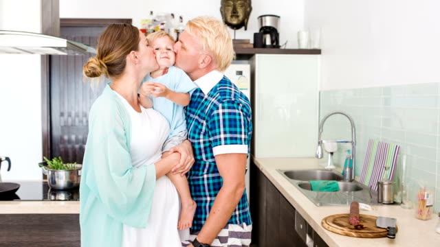 glückliches paar mit kid in the kitchen in den tag. schwangere frau. frühstück. - unfug stock-videos und b-roll-filmmaterial