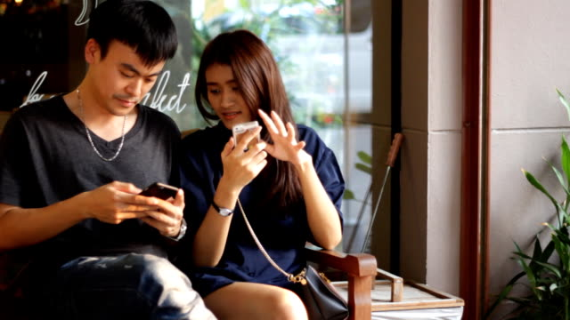 happy couple with smart phone outdoor cafe