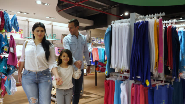 happy couple with their cute daughter shopping for clothes at a store - shopping centre stock videos & royalty-free footage