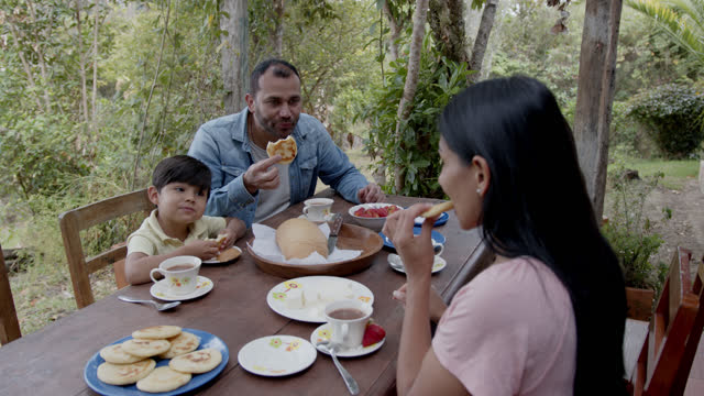 happy couple with their two children enjoying a delicious breakfast at a farm - serving size stock videos & royalty-free footage